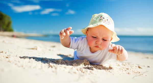 Ребенок играет в песке на пляже
