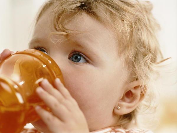 Ребенок пьет из оранжевой кружки
