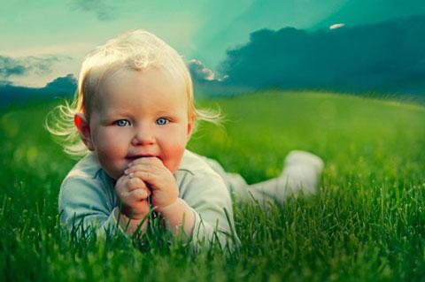 грудничок лежит на зеленой траве