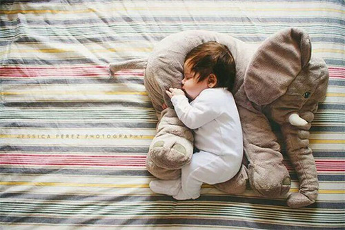 малыш спит на подушке в форме слона