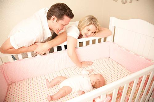 родители укладывают спать ребенка