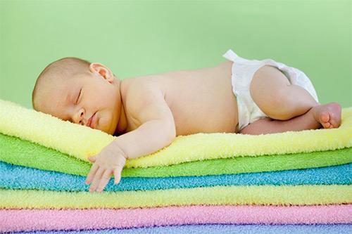 малыш спит на стопке полотенец