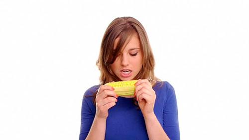 девушка ест вареную кукурузу