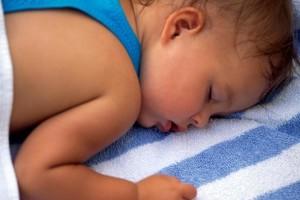 Ребенок спит на полотенце