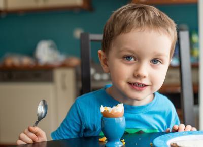 мальчик ест вареное яйцо