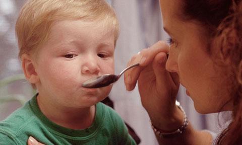 мальчик пьет лекарство из ложки