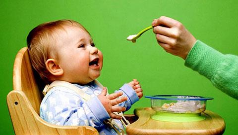 довольный малыш кушает кашу