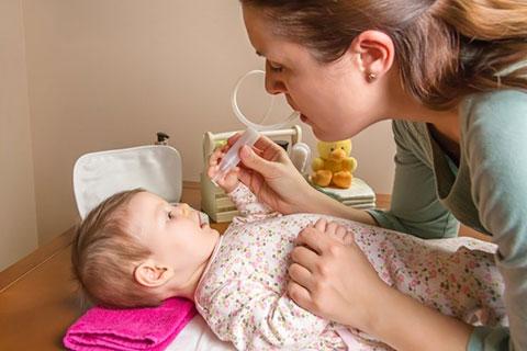мама закапывает нос малышу