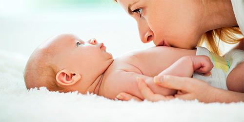 мама целует в животик ребенка