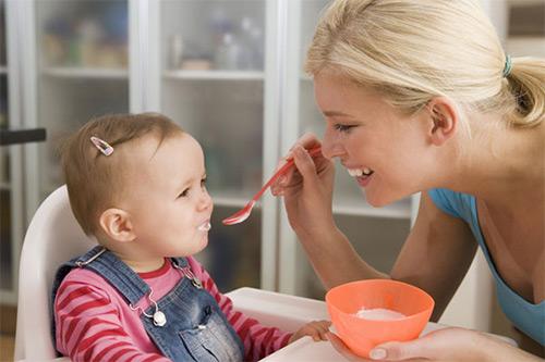 мама кормит девочку